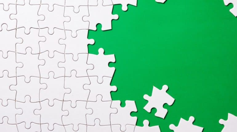 White jigsaw puzzle on green background
